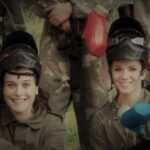 2 girls with paintball masks and guns smiling