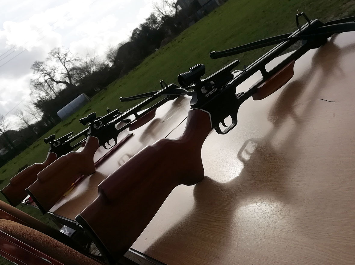 crossbows on table silhouetted against the sun